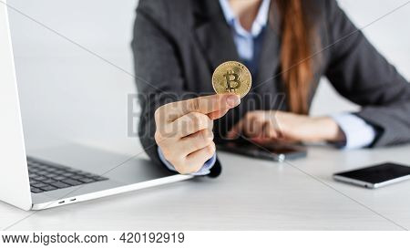 Businesswoman Trader Holding Bitcoin Cryptocurrency In The Office With Laptop And Smartphones. Crypt