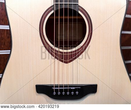 A Six-string Acoustic Guitar. A Fragment Of The Guitar Case In Close-up.