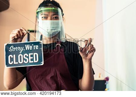 Cute Asian Female Hairdresser With Eye Mask, Protective Mask In Black Tshirt And Apron With A Metal