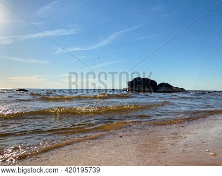 Sea View With Calm Waves And A Huge Rock On The Sea Shore Washed By Blue Sea Water. A Lush Summer Da