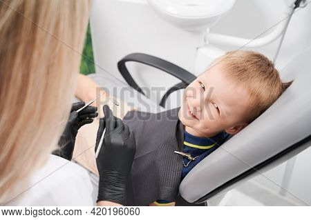 Adorable Male Kid Looking At Camera And Smiling While Female Dentist Holding Dental Mirror And Explo