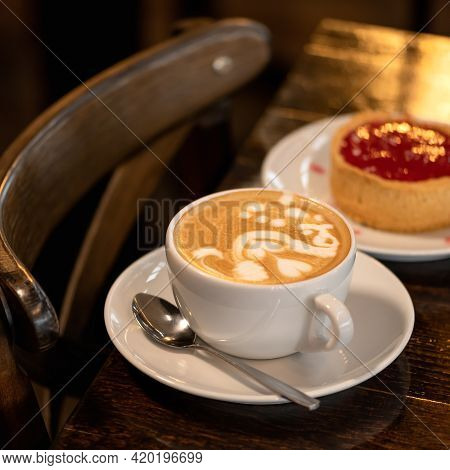 Cappuccino Coffee With Berry Dessert On Dark Background. Sweets And Cup Of Creamy Drink With Froth.