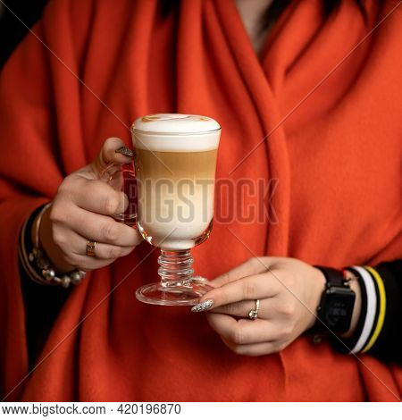 Woman In Red Poncho Holding Glass Cup Of Coffee Drink. Glass Of Latte Coffee With Froth In Female Ha
