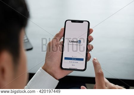 Chiang Mai, Thailand, Apr 06, 2019 : A Man Holds Apple Iphone Xs With Linkedin Application On The Sc