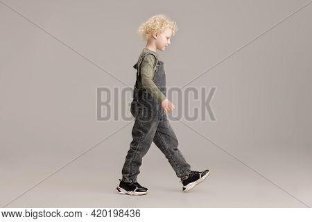 Happy Caucasian Little Albino Boy Posing Isolated Over Gray Studio Background.