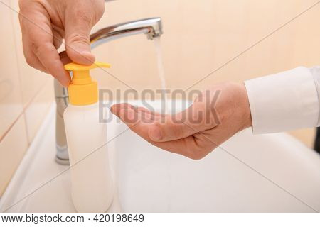 hand washing with soap or gel under running water in the washbasin, cleanliness and hygiene, men's hands dressed in a white shirt