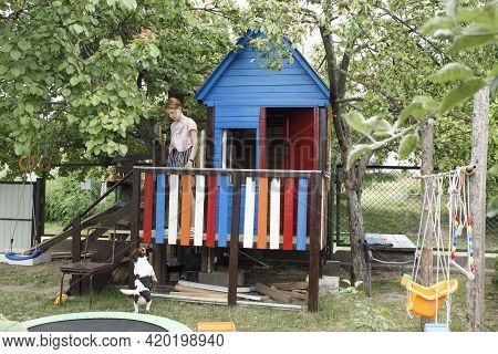 Summer House Gazebo For Children In The Courtyard Of A Private House. A Girl Plays With A Dog In The