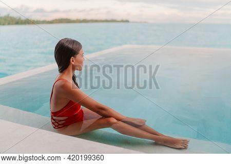 Spa wellness relaxation relaxing Asian woman in swimming pool looking at ocean view at dusk, well-being zen travel vacation at luxury resort overwater villa private room.