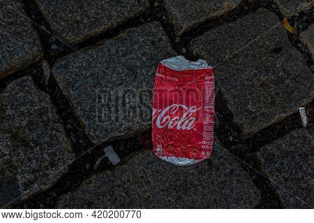 Pilsen, Czech Republic, 1.09.2019 - Red Flattened Coke Can On Gray Old Stone Sidewalk. Coca-cola Is