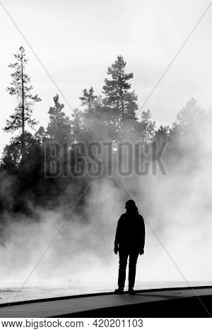 Silhouette of Person by steaming steam rising pond pool adventure Yellowstone National Park geyser