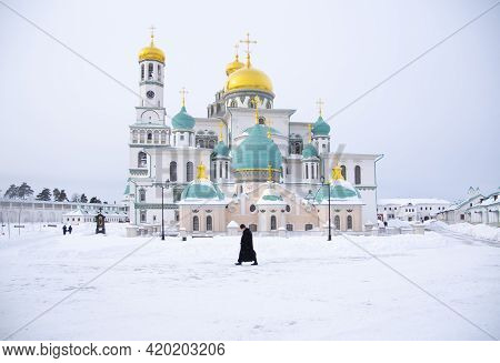 Russia, New Jerusalem Monastery, February 2021. A Majestic Temple Against A Cloudy Sky. The Priest W