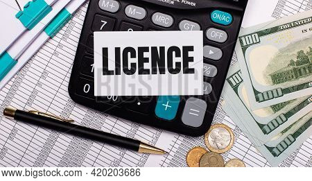 On The Desktop Are Reports, A Pen, Cash, A Calculator And A Card With The Text Licence. Business Con