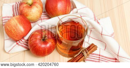 Squeezed Apple Juice In The Glass With Kitchen Towel And Apples With Cinnamon At The Background On T