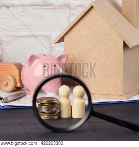 Wooden Family Figurines And  Pink Ceramic Piggy Bank On Blue Background. Concept Of Accumulating Cas