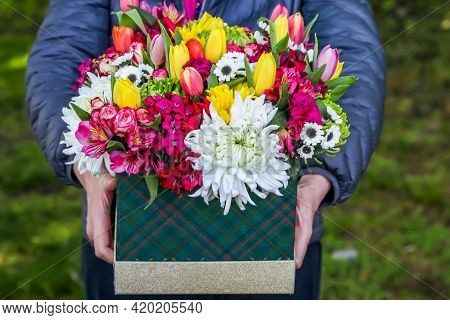 Person is holding box with beautiful flowers