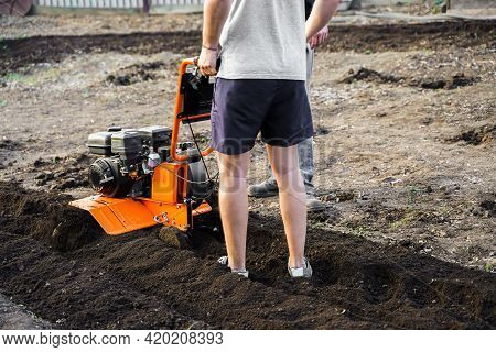 A Man Plows The Ground With A Tillerblock In The Garden. Farmer Man Plows The Land With A Cultivator