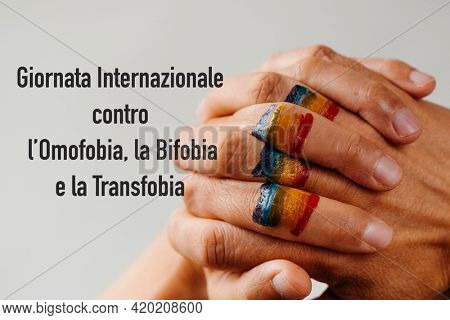 the rainbow flag painted in the clasped hands of a young person and the text international day against homophobia, transphobia and biphobia written in italian against a white background