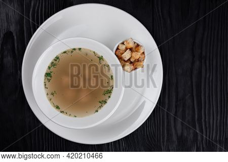 Chicken soup bouillon in a plate with chicken meatballs and croutons