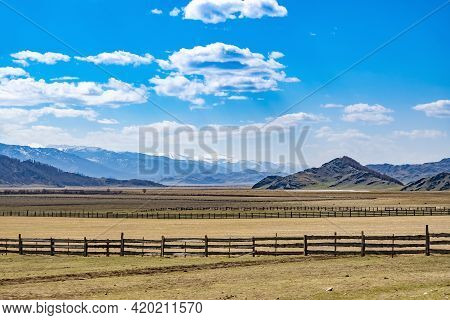 Landscape Of Various Rocky And Snow-covered Peaks Of The High Altai Mountains On A Flat Plateau Agai