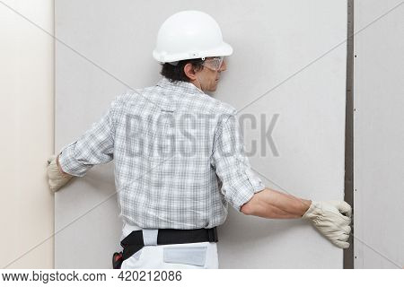Man Drywall Worker Installing Plasterboard Sheet To Wall. Wearing Hardhat, Work Gloves And Safety Gl