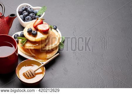 Healthy breakfast with pancakes and herbal tea. Homemade american pancakes with berries and honey. With copy space