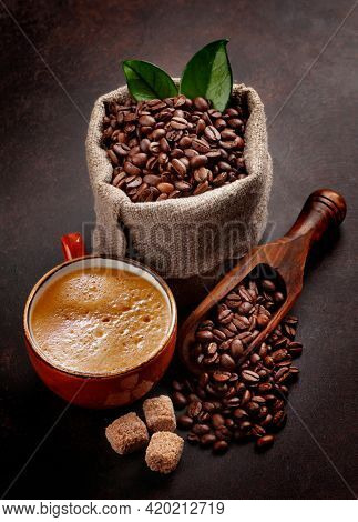Roasted coffee beans in burlap bag, brown sugar and cup of hot espresso coffee on stone table