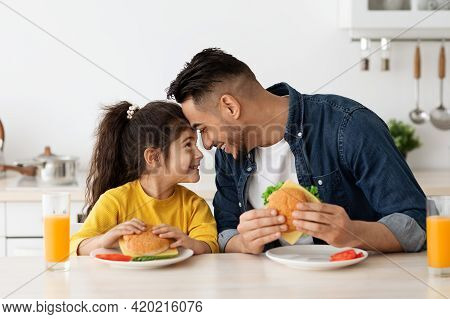 Happy Loving Arab Dad And Daughter Eating Sandwiches In Kitchen And Bonding