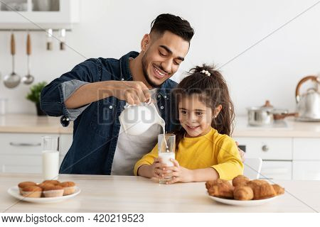 Happy Arab Dad And Daughter Eating Pastry And Drinking Milk In Kitchen