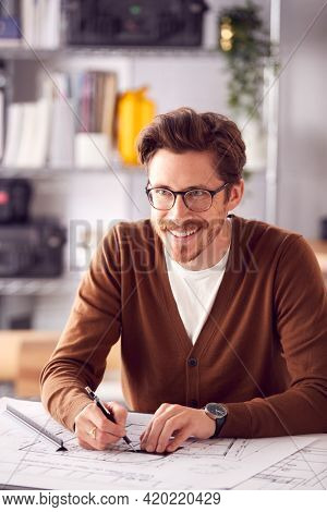 Male Architect At Desk In Office Amending Building Plans
