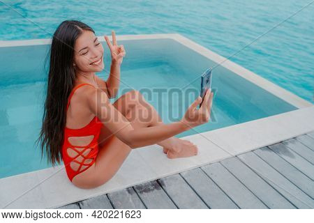 Social media travel influencer taking selfies at luxury hotel infinity pool overwater bungalow suite sunbathing in fashion swimsuit. Asian beauty model woman on vacation.