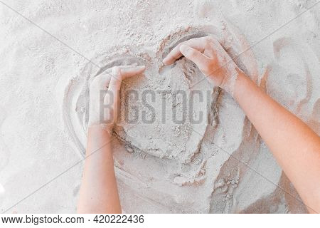 The Hand Of A Young Girl Draws A Heart On The White Beach Sand Close-up. Symbol Or Sign Of Love Conc