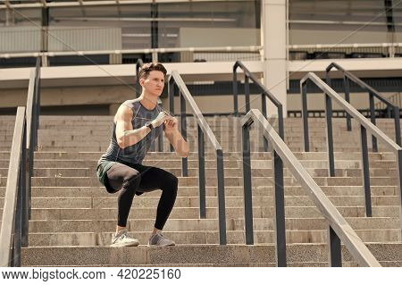 Exercising And Healthy Lifestyle Concept. Man Doing Squats Outdoor. Man With Fitness Watch Exercisin