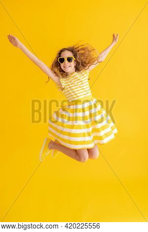 Happy Child Jumping Against Yellow Summer Background
