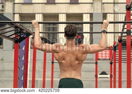 Strength And Motivation. Muscular And Strong Guy Exercise. Young Athlete Does Pull Up. Young Fit Man
