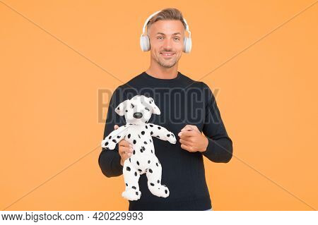 Just Let The Music Play. Happy Man Point Finger Playing With Toy Dog. Fun And Entertainment. Play An