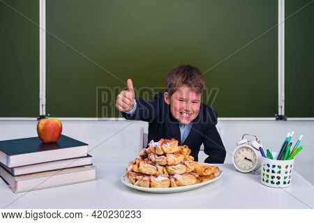 Junior Schoolboy During Lunch In A School Class. Unhealthy And Healthy Nutrition For Schoolchildren