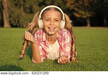 Just Nice Day. Relax On Green Grass In Headphones. Small Girl Listen Audio Book. New Technology For