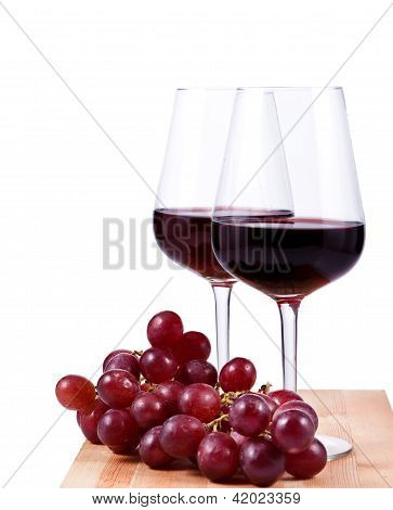 Two Wine Glasses With Red Wine And Grapes