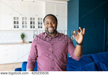 Happy Guy Holding The Keys With Keychain In Form Of Little House. Smiling African-american Man Holds
