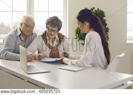 Old Married Family Couple Signing Contract Agreement At Bank Manager Meeting