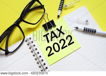 Tax 2022. Text On Bright Yellow Sticker. On The Blanket. Yellow Background And Black Glasses Near Th