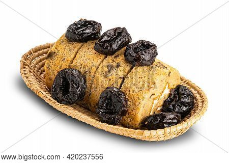 High Angle View Of Prune Sponge Cake Roll And Dried Pitted Prune In Bamboo Basket On White Backgroun