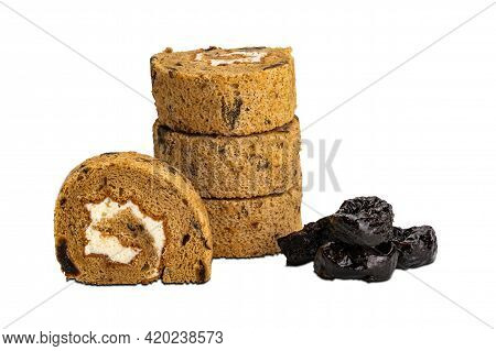 Closeup View Stack Of Prune Sponge Cake Roll And Pile Of Dried Pittrd Prune On White Background With