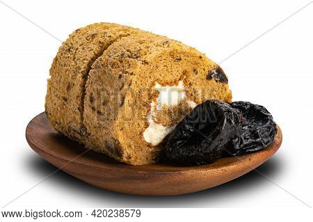 Closeup View Of Sliced Prune Sponge Cake Roll With Pittrd Dried Prune In Wooden Plate On White Backg