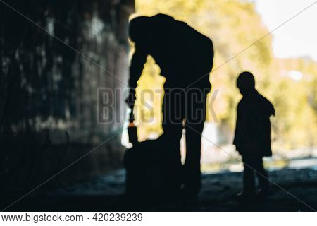 Poor Beggar Man With Son Or Daughter Collecting Bottles To Buy Food
