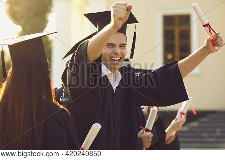 Happy Smiling University Graduate In Mantle Holding Diploma In Raised Hand And Expressing Happiness