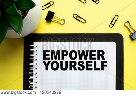 Notepad With Text Empower Yourself On The Office Desk With A Plant, Stationery. A Blank Notepad For