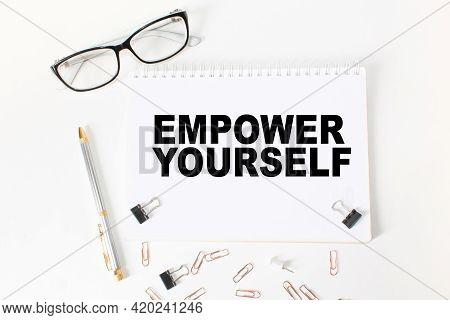 Notepad With Text Empower Yourself On The Office Desk With Stationery. A Blank Notepad For Entering