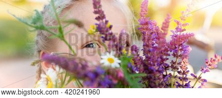 Close-up Portrait Of Little Cute Caucasian Blond Kid Girl Peeking And Hiding Holding Bouquet Of Salv