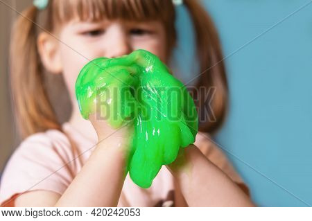 A Small, Cute Girl Is Holding A Green Slime On A Blue Background. A Child Plays With A Slimy Toy At